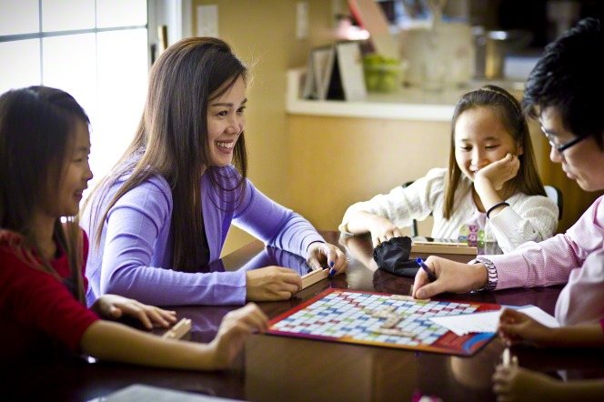 A mother and father sit at a table with their two daughters and play a word game together.