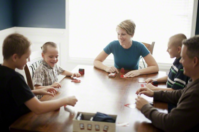 A mother and father sit at a dining room table and play a game with their four sons.