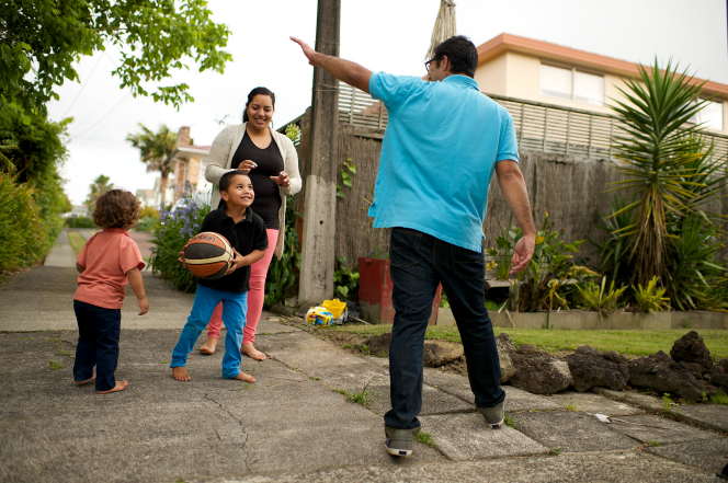 A mother and father play basketball outside with their two young children.