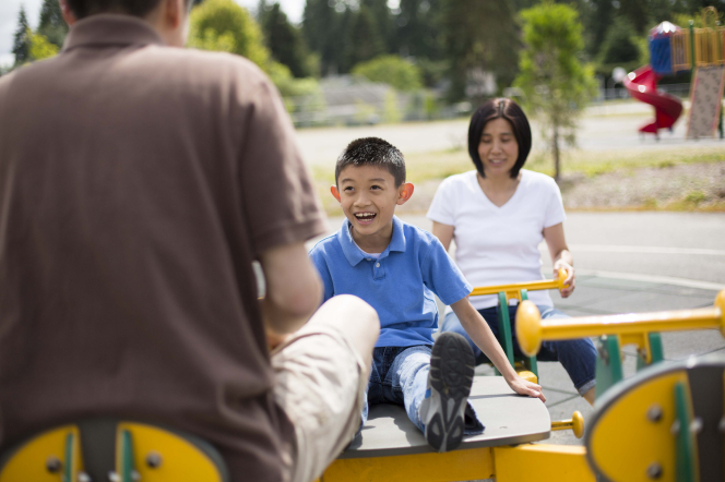 A mother and father play with their son on a large yellow toy at the playground.