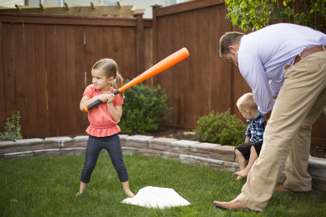 A young girl stands next to a base, holding an orange bat, with her father and younger brother nearby.