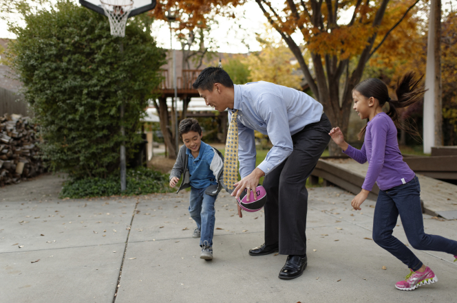 A father, still dressed in work clothes, plays basketball in the driveway with his young son and daughter.
