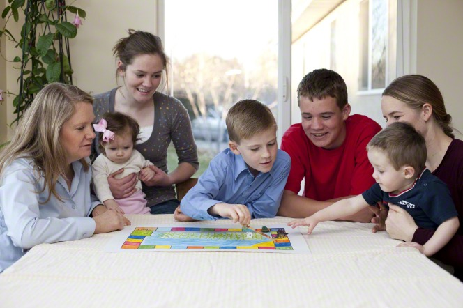 A mother and her three sons and three daughters play a board game together at a table next to a window.
