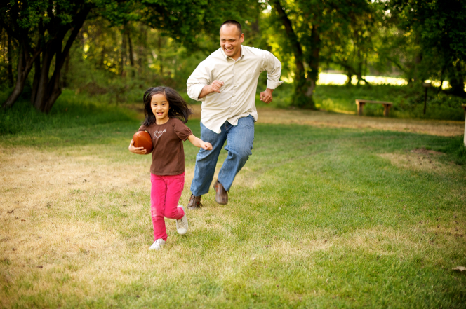 A father plays football outside with his daughter, who is running in front of him with the ball.