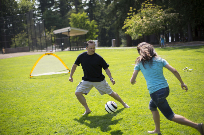 A father kicking a soccer ball with his daughter, who is running up to him on a grass field.