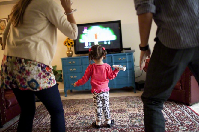 A mother and father standing while playing a video game on the TV with their young daughter standing in front of them in their living room.