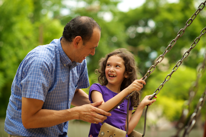 A father in a blue plaid shirt pushes his young daughter on a swing at a park.