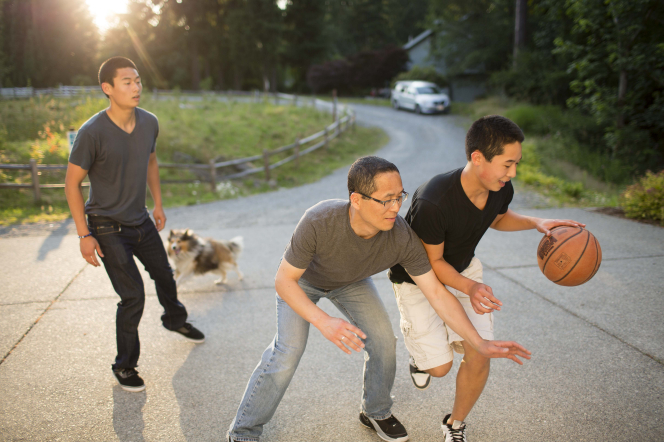 A father plays basketball with his two teenage sons in their driveway, with their dog running behind them.