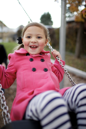 A girl in a pink coat and striped pants plays on a swing at a park.