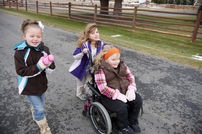 A girl pushes another girl in a wheelchair while another girl walks beside them on a road.