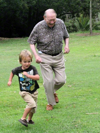 A grandfather laughing and chasing his young grandson outside.