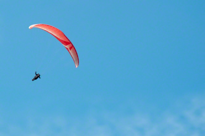 A person hanging down from a red and white hang glider against a clear blue sky.