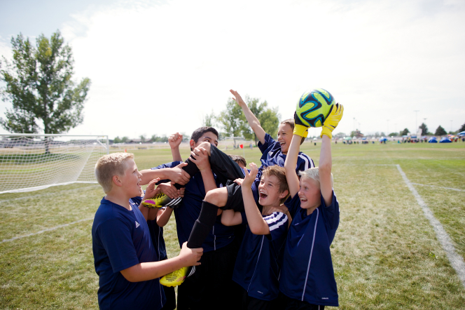 A team of boys on a soccer field cheers after a game by lifting one boy onto their shoulders while another boy holds a soccer ball in the air.