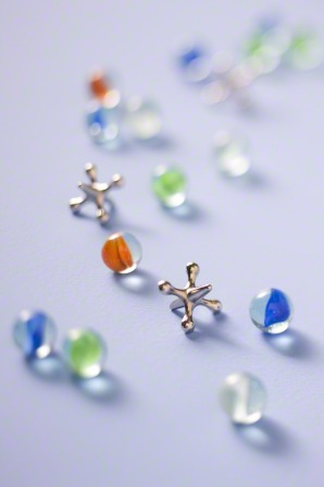 An image of clear, blue, green, and orange marbles next to two jacks on a table.