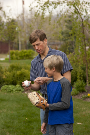 A father stands and holds a baseball while his son stands next to him, holding the mitt.