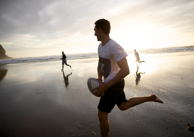 A young man in a white shirt and shorts playing rugby on the beach, running with the ball as the sun sets over the ocean.