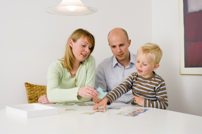 A mother and father sit at a table with their young son and play cards with him.