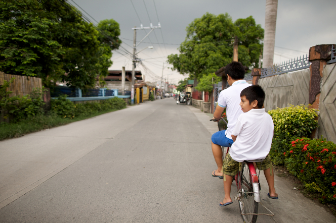A boy in the Philippines pedals a bike down a street, with his younger brother sitting on a metal rack behind the bike's seat.