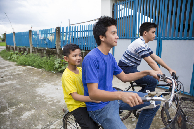 A young man in a blue T-shirt rides a bike with a boy in a yellow T-shirt sitting behind him and another young man riding next to them.