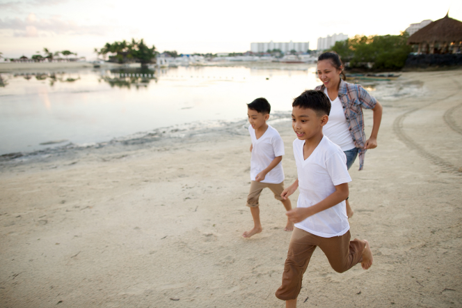 Two young boys in white shirts and tan pants running on a beach in front of their mother in a plaid shirt.