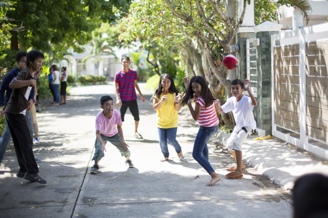 A group of young men and women from the Philippines toss a ball in the air while standing in a street partially shaded by the overarching trees.