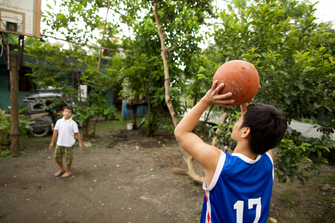 A young man in a blue jersey reaches up to throw a basketball on a dirt court, with his younger brother watching up ahead.