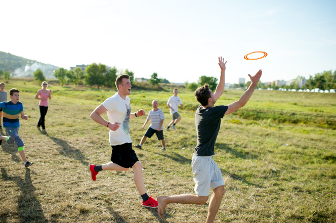 A young man runs in a grass field and reaches for an orange Frisbee with other young men and women running behind him.