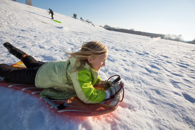 A young girl lies down on a sled and rides it down a snow-covered hill.