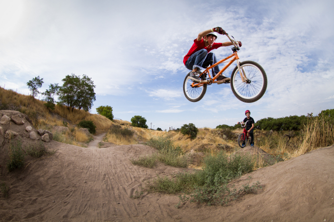 Two teenage boys go dirt biking, and one does a jump in the air while the other waits in the background.