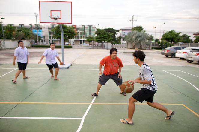 A young man runs and dribbles a basketball while playing on an outside court with three other young men.