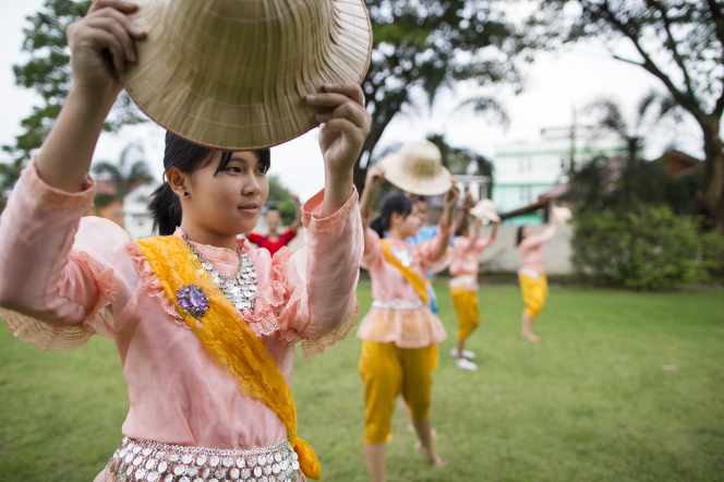 Young women from Thailand dressed in native costumes hold wide-brimmed straw hats while dancing outside.