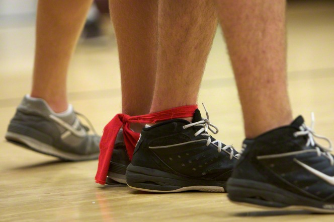 Two people have a red band tied around their ankles, close to their tennis shoes, as they prepare for a three-legged race.