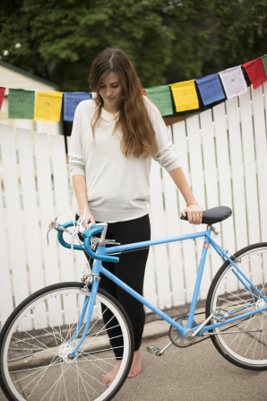 A woman pushing her blue bike along next to a white fence.