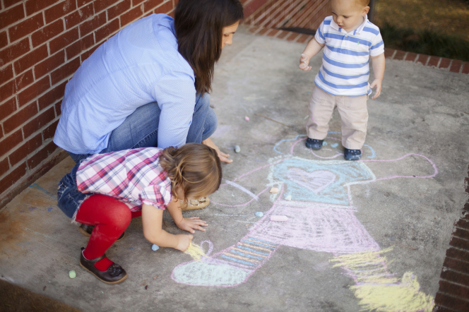 A mother kneels on the cement beside her son and daughter as they use chalk to draw a girl on the sidewalk.