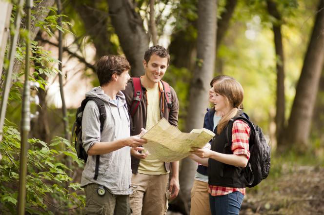 A group of four young adults wearing backpacks look at a map together while hiking in the woods.