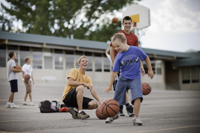 Two young men play basketball on a school basketball court with a boy with Down syndrome who is wearing a blue T-shirt, jean shorts, and tennis shoes.