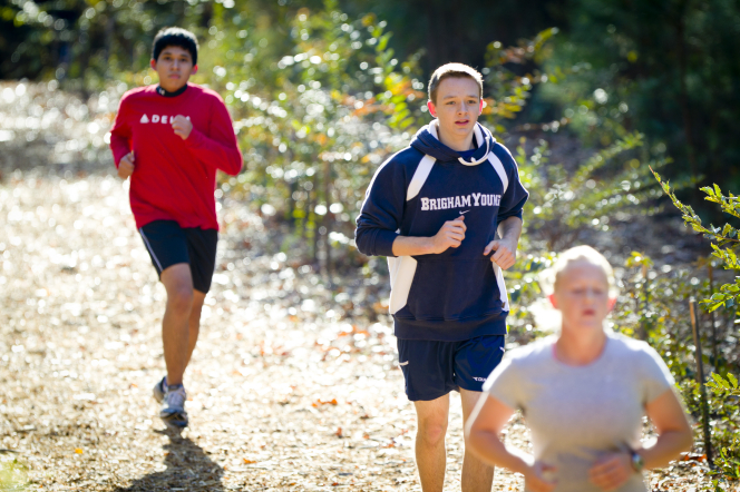 Two young men in long-sleeved shirts and shorts run behind a girl on a dirt trail with the sun shining on their backs.