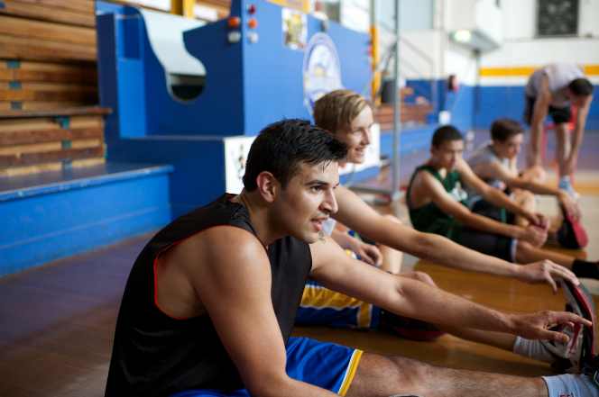 Young men stretch and prepare for a basketball game on the side of a court.