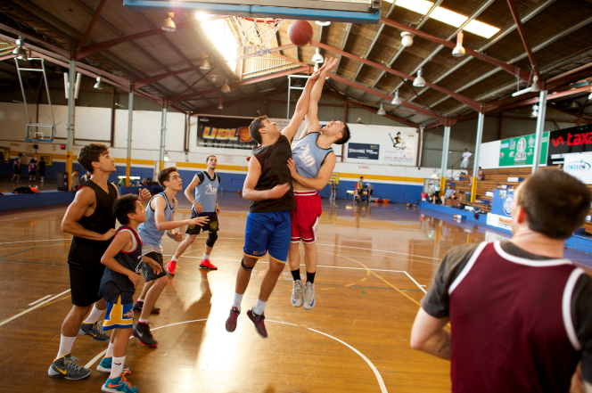 Two basketball players jumping and reaching for the ball near the basketball hoop in a gym, with teammates watching from the sides.