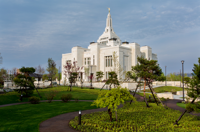An angled view of the Sapporo Japan Temple with green grass and trees.