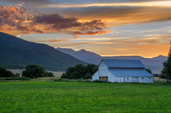 A sunset over a mountain near farmland with a green field, trees, and a large white barn.