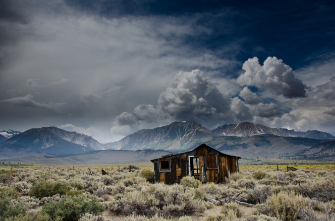 A run-down cabin in a field, with a mountain range covered with clouds in the background.