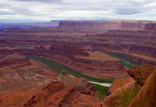 The dark green Colorado River runs through red rock canyons in southern Utah, with clouds covering the sky.