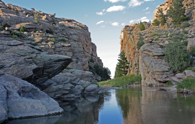 The historic site Devil's Gate in Wyoming, consisting of tall rocky ledges lining a small body of water.