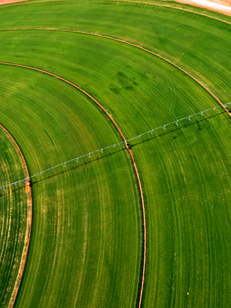 An aerial view of a water pivot on a circular green field.