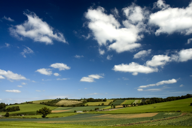 The countryside in Somerset, England, with green hills and fields, and the blue sky and clouds above.