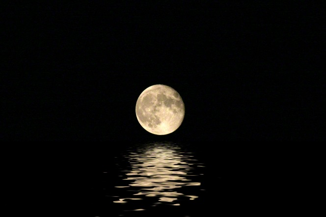A full moon in a pitch-black sky reflects on the water.