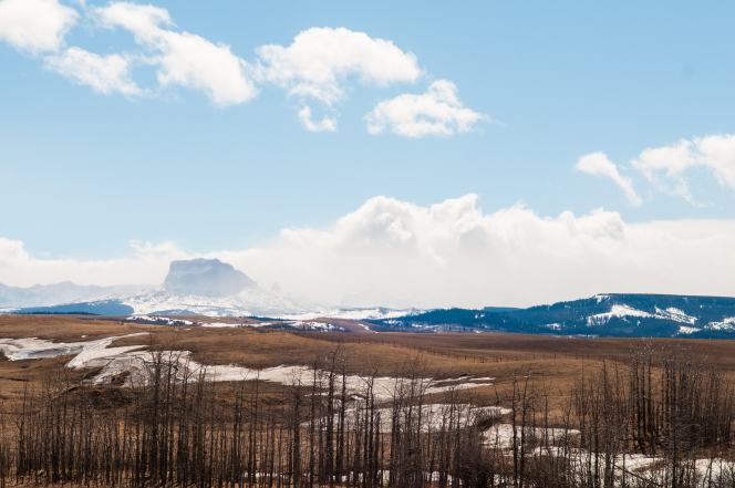 A mountain range in Canada in the winter, with brown grassland, snow, and a cloudy sky.