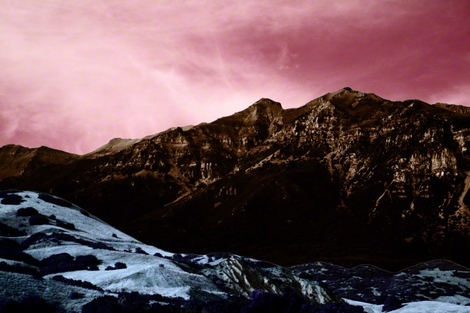 A pink sky hangs over a valley and a rocky mountain range.