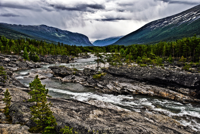 A river runs through the mountains and a valley in Norway, with green pine trees and a cloudy sky.